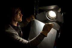 Lighting technician and studio light. Lighting man placing a sheet of diffuser on a studio light in a Television studio Stock Photography