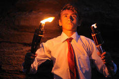 Lighting with torch. Young businessman lighting with torch in a cave Royalty Free Stock Image