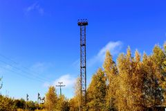 Lighting tower on the railway against the background of the autumn forest Royalty Free Stock Photography