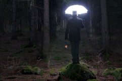 Lighting umbrella. A mysterious man with a lighting umbrella in the forest Stock Photography