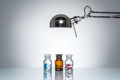 Lighting up bottle drugs pill medicine  with desk lamp Royalty Free Stock Photo