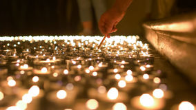 Lighting Up Candles of Prayer. Man of the belief refiring candles of prayer placed on the floor Stock Photo