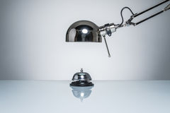 Lighting up hotel bell for calling service with desk lamp. On round studio lighting Stock Photos