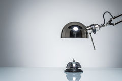 Lighting up hotel bell for calling service with desk lamp. On round studio lighting Stock Image