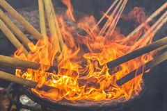 Lighting up joss stick with fire flames. Asian traditional r Stock Image