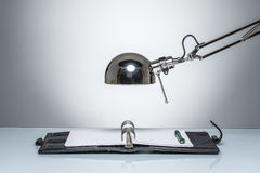 Lighting up notebook diary writing with desk lamp. On round studio lighting Royalty Free Stock Photography