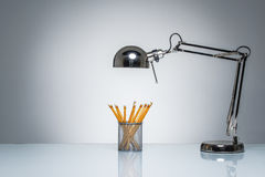 Lighting up orange pencil holder stationery with desk lamp Stock Images
