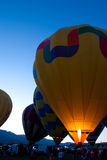 Lighting Up Portrait. Yellow hot air balloon with lit pilot light in dusk light Royalty Free Stock Image