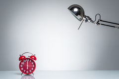 Lighting up red alarm clock with desk lamp. On round studio lighting Royalty Free Stock Photography