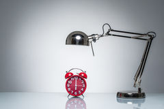 Lighting up red alarm clock with desk lamp Stock Images