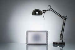 Lighting up tablet touchpad note with desk lamp Royalty Free Stock Photos