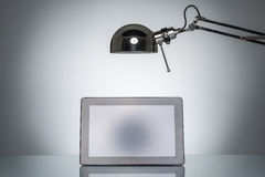Lighting up tablet touchpad note with desk lamp Stock Photos