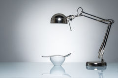 Lighting up white ceramic bowl silver spoon with desk lamp Royalty Free Stock Images