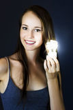 Lighting The Way To Innovation. Beautiful smiling woman holds a shining light bulb in a concept of ideas and inspiration when lighting the way to innovation Royalty Free Stock Image