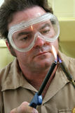 Lighting Welding Torch. A welder, wearing safety goggles, lighting a welding torch royalty free stock image