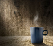 Lighting from window with hot blue coffee cup in hardwood room w Royalty Free Stock Photography
