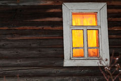 Lighting window of rural log house Royalty Free Stock Images