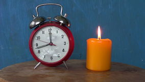 Lighting yellow candle and retro clock on table stock video footage