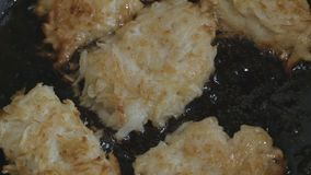 Lightly fried hash browns are fried in a pan in oil the camera moves from right to left stock video