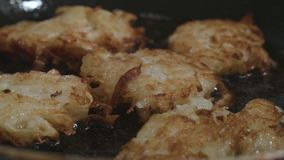 Lightly fried hash browns are fried in a pan in oil focus shift stock video footage