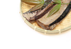 Lightly roasted bonito on a bamboo colander. Pictured lightly roasted bonito on a bamboo colander with leaf Royalty Free Stock Photography
