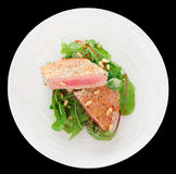 Lightly seared tuna steak, isolated. Lightly seared tuna steak with sesame and fresh salad isolated on black Royalty Free Stock Photo