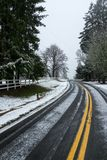 A lightly snow covered road just outside Portland, Oregon, USA, the double yellow lines leading off into the distance. No traffic royalty free stock photography