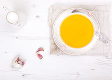 Lightly spiced carrot soup in a bowl, on the white table. Top view Royalty Free Stock Image