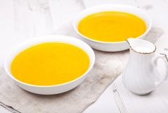 Lightly spiced carrot soup in bowls, on the white table. Lightly spiced carrot soup in two bowls, on the white table Royalty Free Stock Image