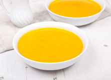 Lightly spiced carrot soup in bowls, on the white table Stock Image