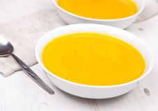 Lightly spiced carrot soup in bowls, on the white table Royalty Free Stock Image
