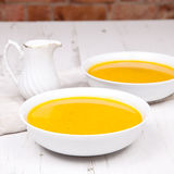 Lightly spiced carrot soup in bowls, on the white table Stock Images