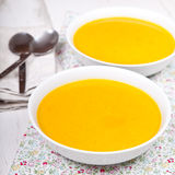 Lightly spiced carrot soup in bowls, on the white table Royalty Free Stock Photo