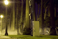 Lightly Watered. Light shine bright as Sprinklers water the grass royalty free stock image