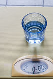 Lightness. Glass of water on a libra Royalty Free Stock Photos