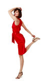 Lightness of being. Beautiful flirting brunette in elegant red silk dress standing on one leg Royalty Free Stock Images