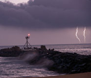 Lightning. Strike over ocean and jetty Stock Image