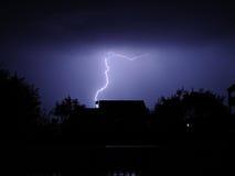 Lightning. Above house on dark blue sky Stock Image