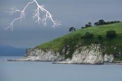 Lightning above green foreland. Seascape. Overcast sky Stock Photos