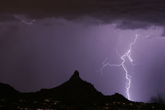Lightning Bolt Hitting beside Pinnacle Peak. Hugh Lightning Bolt striking beside Pinnacle Peak. Purple in colore Stock Photos
