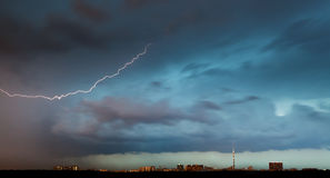 Lightning bolt in storm clouds over city Royalty Free Stock Photography