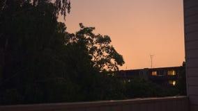 Lightning bolt strike over urban city area surrounded by trees. Flash of thunderbolt light on a rainy dark night. Climate change