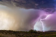 Lightning bolt strikes next to a microburst in a thunderstorm. Lightning bolt strikes next to a microburst of heavy rain in a monsoon thunderstorm stock photo