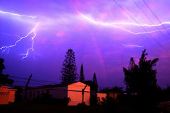 Lightning Bolts. And thunder in a dark violet sky over houses stock photo