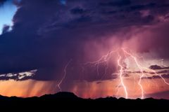 Lightning bolts strike from a storm at sunset. Lightning bolts strike a mountain range in the Arizona desert during a summer monsoon thunderstorm at sunset Royalty Free Stock Photos