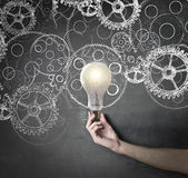 Lightning bulb. With gear wheels Royalty Free Stock Image