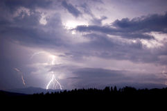 Lightning between the clouds. Powerful storm lightning visible between blue clouds Stock Photography