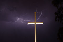Lightning and the Cross. Lightning thunderstorm with lightning stiking behind a religious cross Stock Photography