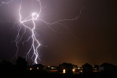 Lightning dancer. Huge lightning bolt hitting near houses stock photo