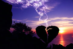 Lightning down to the broken heart-shaped stone,Silhouette Valentine background co. Lightning down to the broken heart-shaped stone on a mountain with purple sky Stock Photos